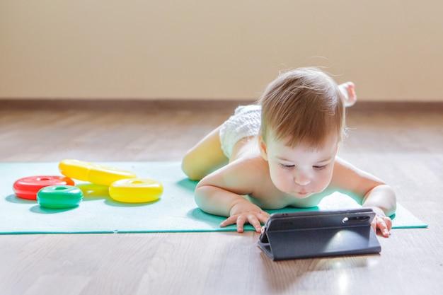 L'enfant a choisi de jouer avec le téléphone plutôt qu'avec des jouets. fille regarde un dessin animé, des jouets traînent. concept de publicité de l'équipement, des téléphones, des jeux éducatifs, de l'enfance, de la journée des enfants, de la maternelle