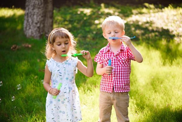 Enfant de cinq ans caucasien fille et garçon soufflant des bulles de savon