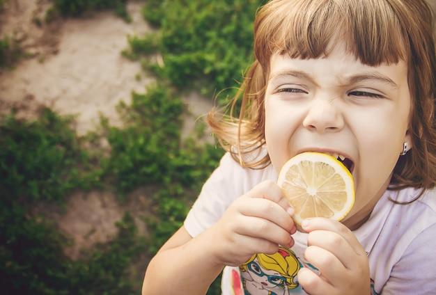 Enfant avec un citron. mise au point sélective. nourriture et boisson.