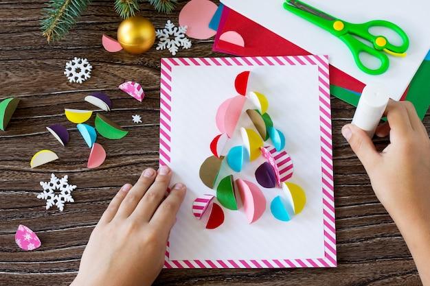 L'enfant colle les pièces carte de voeux d'arbre de noël artisanat fait main pour les enfants