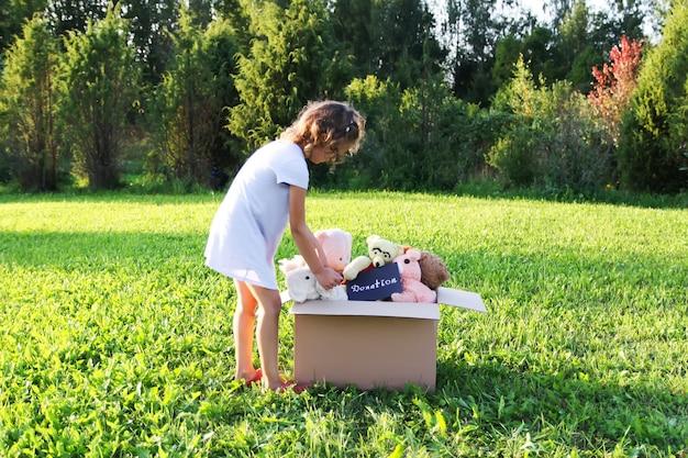 Enfant collectionnant des jouets pour la charité. peluches dans une boîte en carton à l'extérieur.