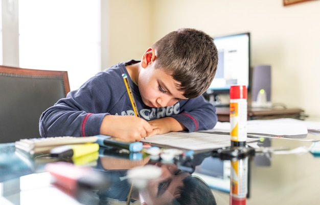 Enfant concentré à faire ses devoirs dans le bureau de papa