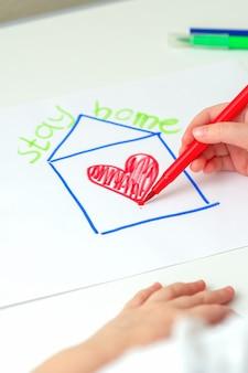 L'enfant de concept de séjour à la maison dessine une maison avec le coeur rouge sur la feuille de papier avec une phrase écrite
