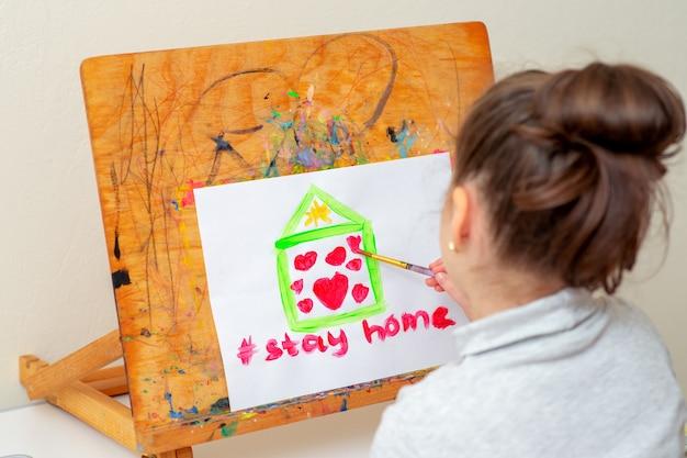 L'enfant de concept de séjour à la maison dessine une maison avec des coeurs rouges sur la feuille de papier avec un écrit
