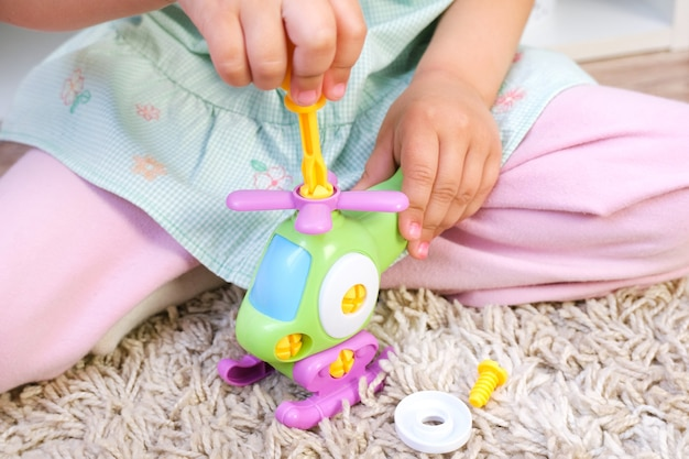 L'enfant construit un hélicoptère avec un tournevis. développement de la motricité fine