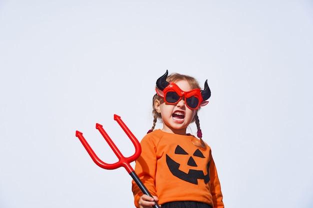 Un enfant en costume de diable avec un trident et des cornes