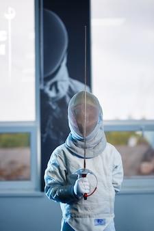 Enfant en costume d'escrime et masque, avec une épée, école d'escrime