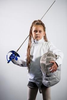 Un enfant en costume d'escrime tient une épée. fille apprenant l'escrime