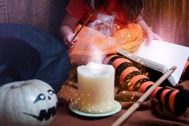 Un enfant en costume de sorcière apprend à faire de la magie à halloween