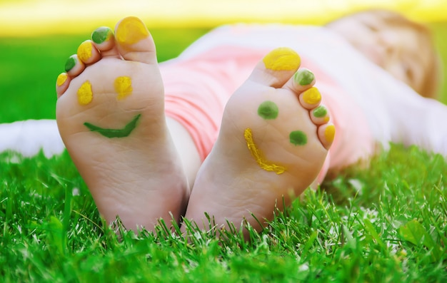 Enfant couché sur l'herbe verte. kid s'amuser en plein air dans le parc du printemps.