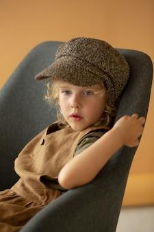 Enfant de coup moyen assis sur une chaise