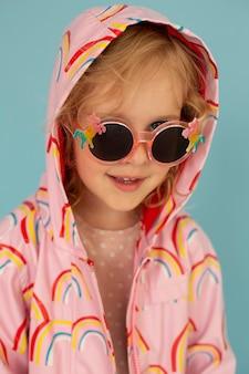 Enfant de coup moyen avec des lunettes de soleil