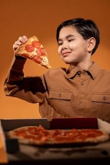 Enfant coup moyen tenant une pizza