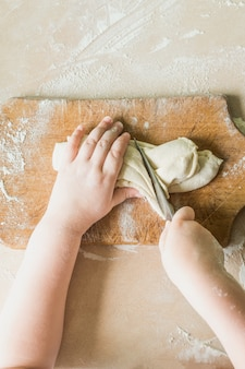 Un enfant coupe la pâte crue