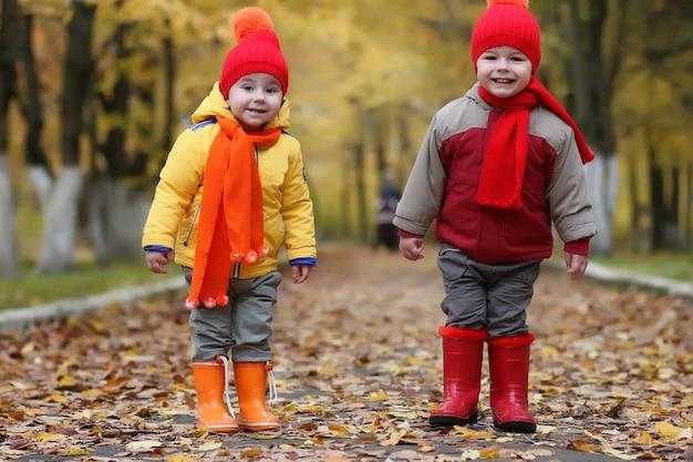 Enfant de couple dans le parc d'automne marchant et s'amusant