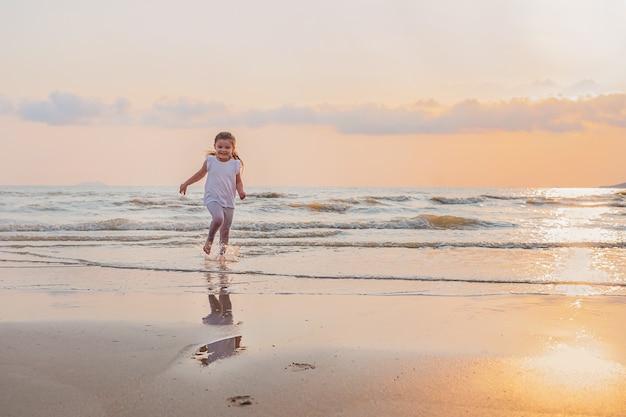 L'enfant court dans l'eau de mer au coucher du soleil le long de la plage
