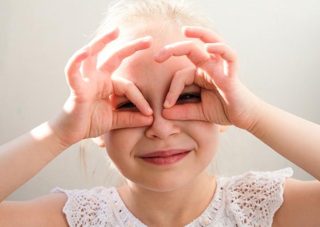 L'enfant a couvert son visage avec ses mains. une fille regarde à travers ses doigts.