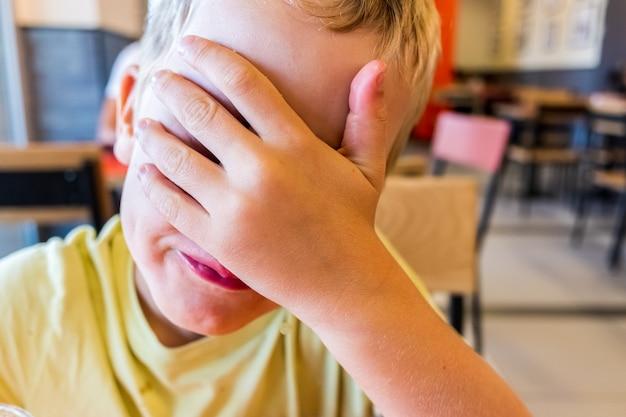 Enfant couvrant son visage surprise avec sa main en souriant.
