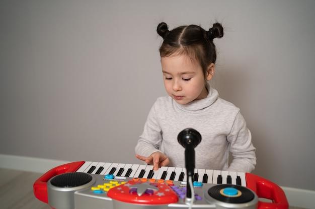 L'enfant créatif joue le synthétiseur. petite fille apprenant à jouer du piano.