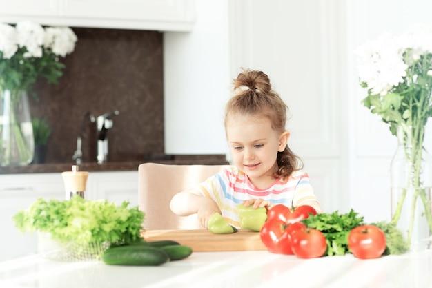 Enfant cuisinier salade de légumes frais et sains vitaminés sur la table sur la cuisine blanche ensoleillée de la cuisine à la maison