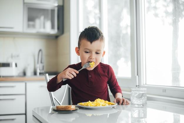 Un enfant dans l'après-midi sur une cuisine lumière blanche dans un pull bordeaux mange une omelette
