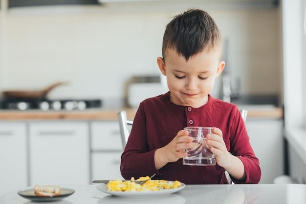 Un enfant dans l'après-midi dans une cuisine de lumière blanche boit de l'eau dans un verre