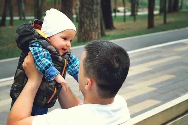 Un enfant dans les bras de son père dans la rue