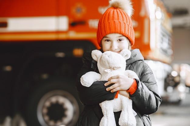 Enfant dans la caserne des pompiers. fille avec un jouet. enfant près du camion de pompiers.