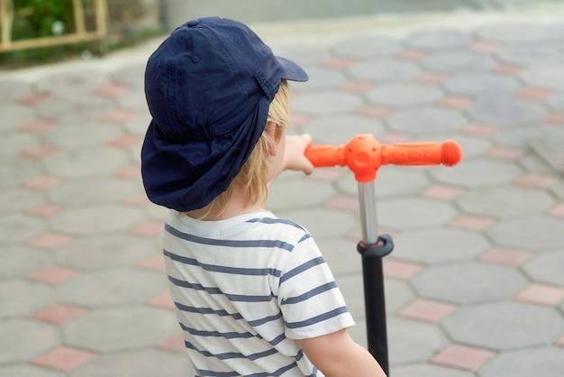 Un enfant dans une casquette de baseball tient le volant d'un scooter