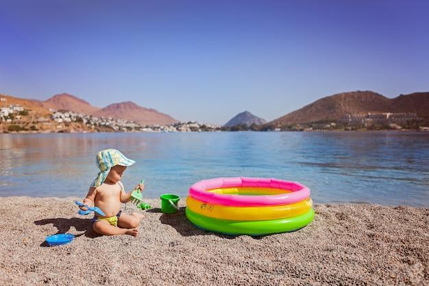 Enfant dans une casquette et maillot de bain assis au bord de la mer sur une plage de galets jouant avec une pelle près de la mer et une petite piscine pour enfants