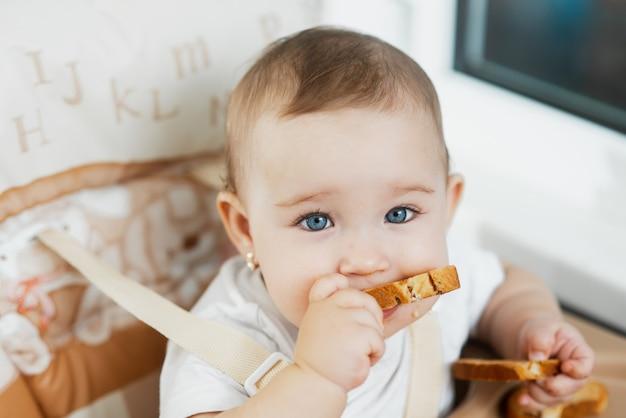 Un enfant dans une chaise haute mangeant un cracker aux raisins secs