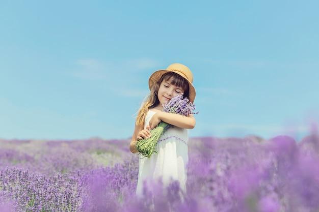 Un enfant dans un champ de fleurs de lavande.