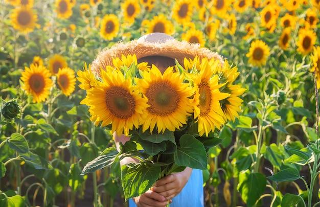 Enfant dans un champ de tournesols en fleurs
