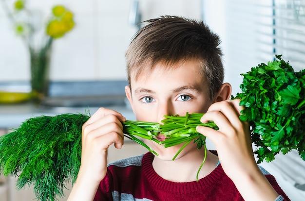 L'enfant dans la cuisine avec de l'aneth et du persil aux herbes, se couvrant le visage comme une moustache
