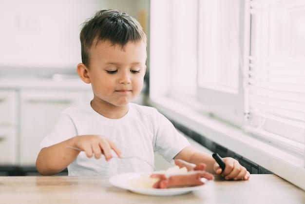 L'enfant dans la cuisine mangeant seul des saucisses et de la purée de pommes de terre
