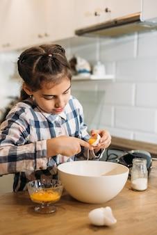 Enfant dans une cuisine. petite fille avec une pâte. enfant dans une chemise bleue et un chapeau de shef blanc