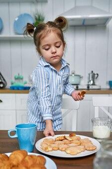 L'enfant dans la cuisine veut manger des biscuits avec du thé