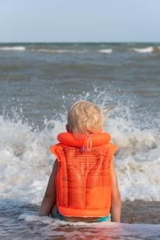 Enfant dans un gilet de bain gonflable au bord de la mer
