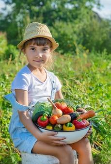Enfant dans le jardin avec des légumes dans ses mains.