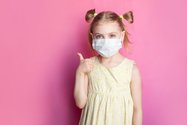 Enfant dans un masque médical sur un mur rose