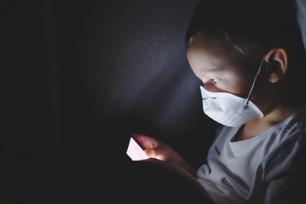 Un enfant dans un masque de protection sous une couverture jouant avec un smartphone, assis sur internet. le concept de passer du temps dans un isolement sûr.