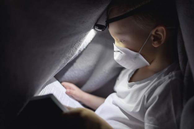 Un enfant dans un masque de protection sous une couverture lisant un livre avec une lampe de poche. le concept de passer du temps dans un isolement sûr.