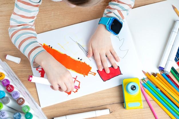 Un enfant dans une montre intelligente dessine dans un album