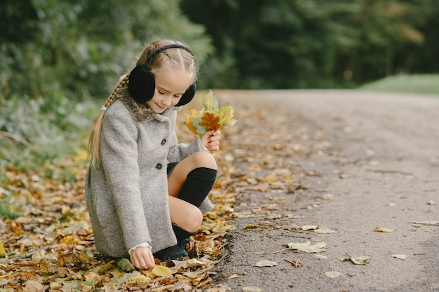 Enfant dans un parc d'automne. enfant dans un manteau gris.