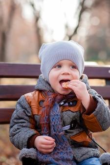 Un enfant dans le parc en train de manger du mandarin