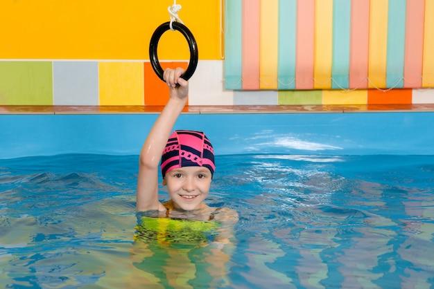 Enfant dans la piscine intérieure excersizing avec anneaux de sport