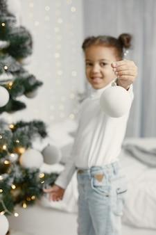 Enfant dans un pull blanc. fille debout près de l'arbre de noël.