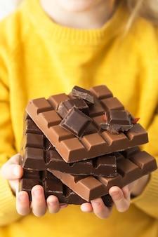 Enfant dans un pull jaune tenant des chocolats. bonbons dans l'alimentation de l'enfant