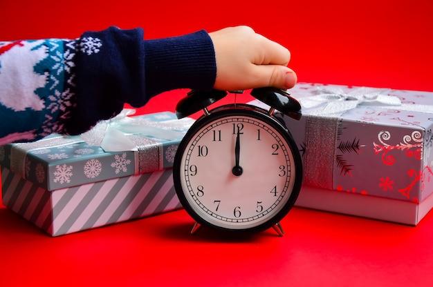 Un enfant dans un pull de noël tient un réveil sur fond rouge cadeaux du nouvel an