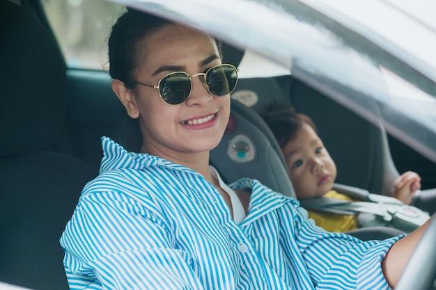 Enfant dans un siège de sécurité près de la mère qui est assis à l'avant de la voiture
